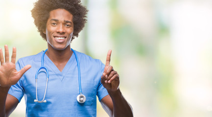Afro american surgeon doctor man over isolated background showing and pointing up with fingers number six while smiling confident and happy.