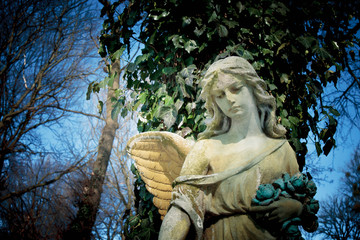 Beautiful sad angel. Vintage styled image of ancient statue.