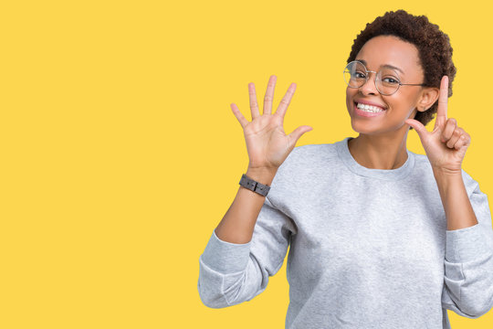 Young beautiful african american woman wearing glasses over isolated background showing and pointing up with fingers number seven while smiling confident and happy.