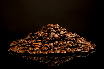 Pile of Coffee beans isolated on gradient brown black background, copy space
