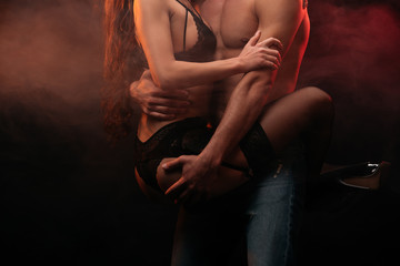 cropped view of passionate couple hugging in smoky room