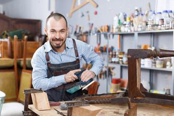 Craftsman repairing antique furniture
