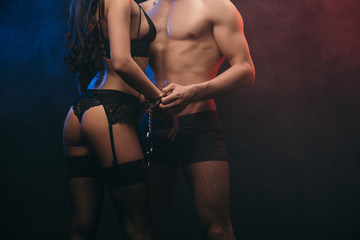 cropped view of passionate couple with handcuffs in smoky room