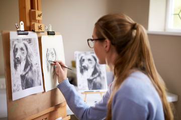 Side View Of Female Teenage Artist Sitting At Easel Drawing Picture Of Dog From Photograph In Charcoal Wall mural