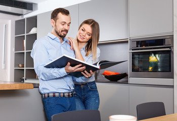 Young beautiful couple standing with book in modern kitchen interior