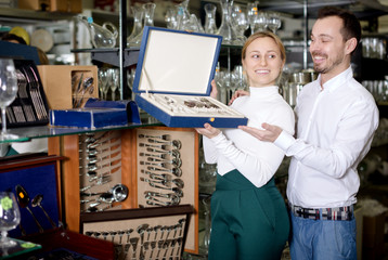 Couple examining cutlery sets in dinnerware store
