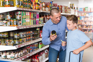 Friendly father and boy making purchases together in store