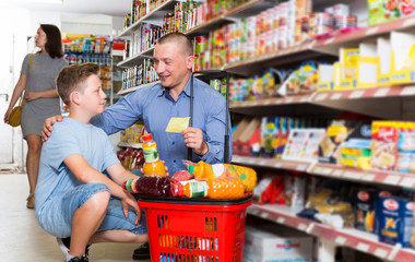 family making purchases together with shopping list