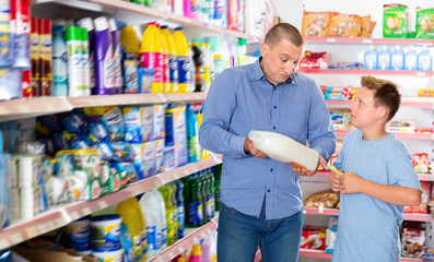 Friendly father and son making purchases together with shopping list in household chemistry store