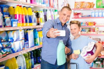 Happy family of father and teen son making selfie while shopping in household chemicals store