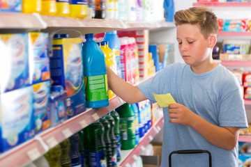 Focused glad boy looking at shopping list