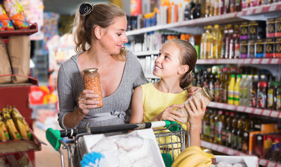 Female and child choosing fresh goods in supermarket