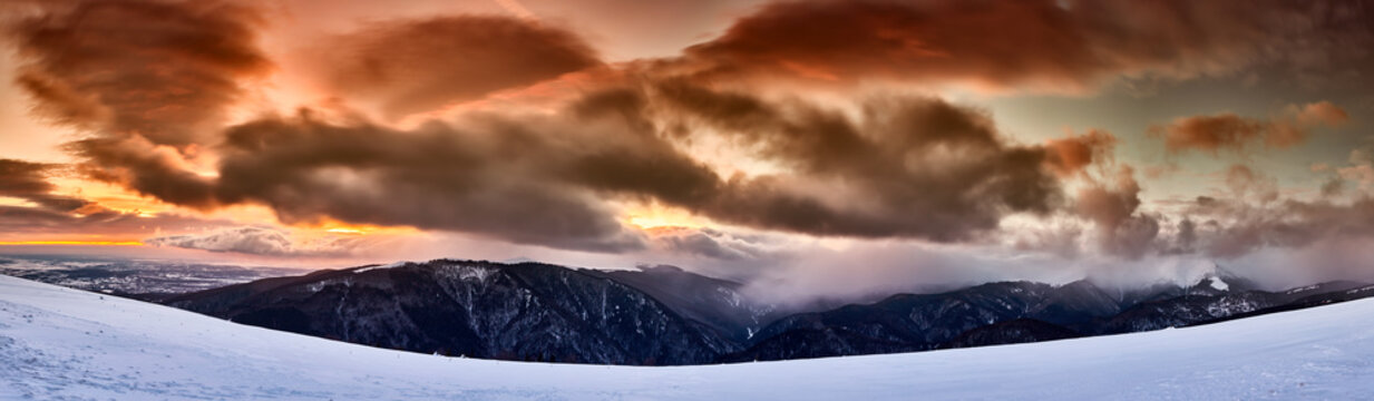 Mountains and snowstorm at sunset