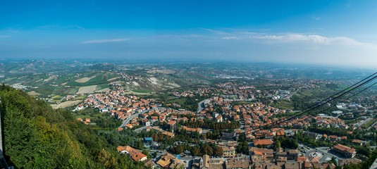 panoramic view on the hilly plain of the foothills of the Apennines with city and funicular cable way from the mountain  Monte Titano, old city of republic of san marino
