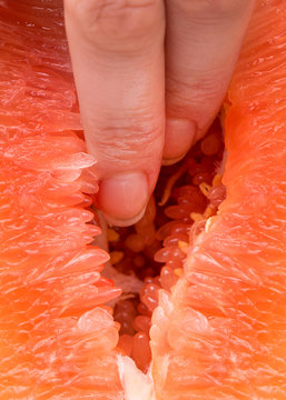 The vagina symbol. Two fingers in grapefruit. Masturbation. Sex concept. Two fingers of the woman are inserted into the juicy flesh of the grapefruit. The concept of female vagina.