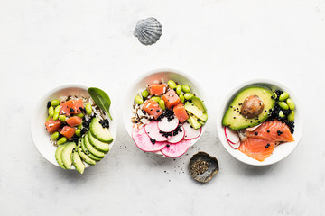 Fresh seafood recipe. Salmon gravlax poke bowl with fresh prawn, brown rice, cucumber, pickled sweet onion, radish, soy beans edamame portioned with black and white sesame. Food concept poke bowl