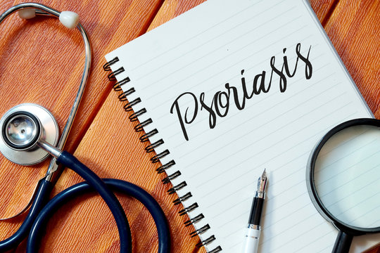 Top view of stethoscope,magnifying glass,pen and notebook written with Psoriasis on wooden background. Health concept.