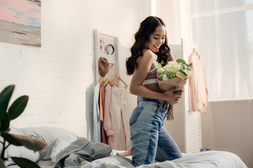 happy attractive asian girl kneeling on bed and holding beautiful flower bouquet