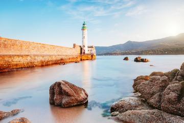 Leuchtturm am Meer am Ufer mit Bergen beim Sonnenuntergang Wall mural