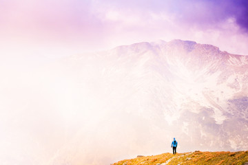 Landscape with silhouette of a standing man  on the mountain peak on the background of foggy weather at colorful sunset in summer.