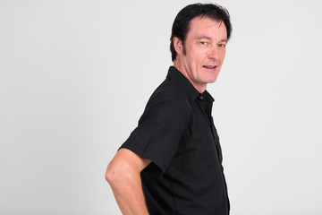 Mature handsome man looking at camera against white background