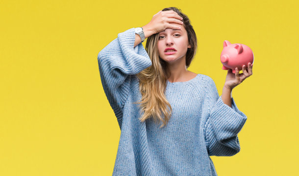 Young beautiful blonde woman holding piggy bank over isolated background stressed with hand on head, shocked with shame and surprise face, angry and frustrated. Fear and upset for mistake.