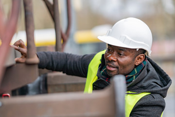 African American mechanic wearing safety equipment (helmet and jacket) checking gear train