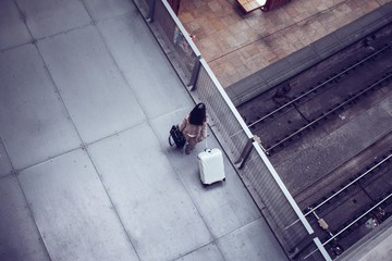 High angle view of woman standing with luggage on bridge