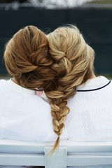 Rear view of women's hair tied together by braid