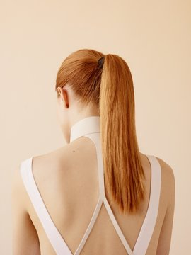 Rear view of woman with ponytail against peach background