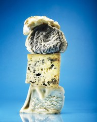 Varieties of cheese stacked against blue background