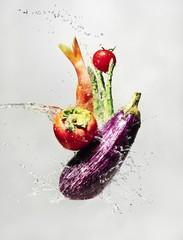 Water splashing on fresh vegetable and fish against white background
