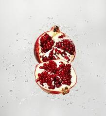 Water splashing on pomegranate against white background