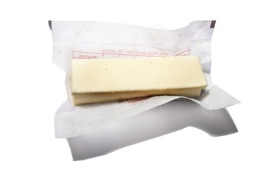 Cheese with parchment paper against white background