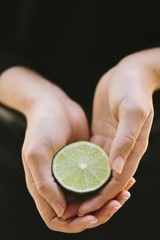 Close up of woman's hand holding lime