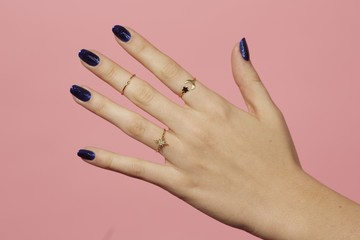 Close up of woman hand with rings against pink background