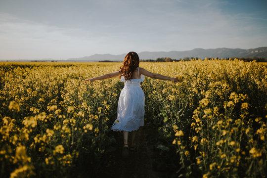 Rear view of woman in white dress walking in field