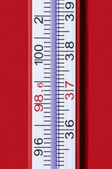 Close up thermometer against red background