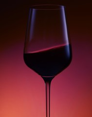 Wine served in wine glass against red background