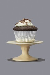 Cupcake on cake stand isolated against gray background