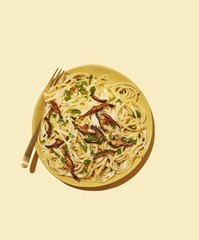 Overhead view of noodles served on plate against white background