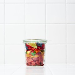 Varieties of fruit in airtight jar against white background