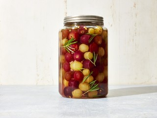 Cherry tomatoes pickle in jar  against white background