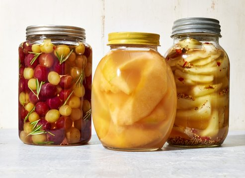 Close up of pickles jars against white background