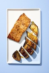 Salmon and eggplant served on plate isolated  on blue background