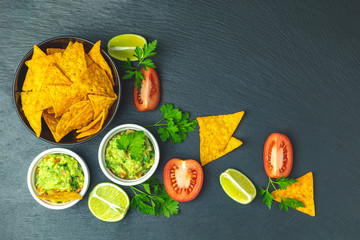 Guacamole and nachos with ingredients on the background of a black stone board