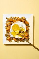 Half fried egg with carrot and legume served on plate against yellow background