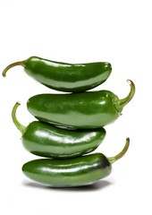 Stack of green chilies against white background