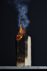 Close up of burning wooden block against black background