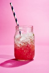 Isolated zombie cocktail drink in jar against pink background